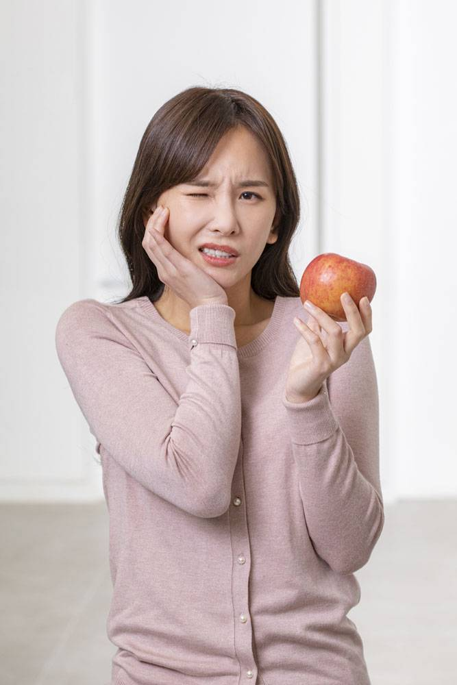 拿着苹果表示牙疼的女性