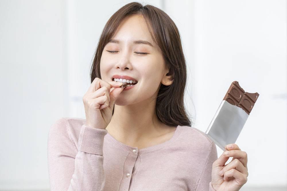 用牙咬吃巧克力板的女性