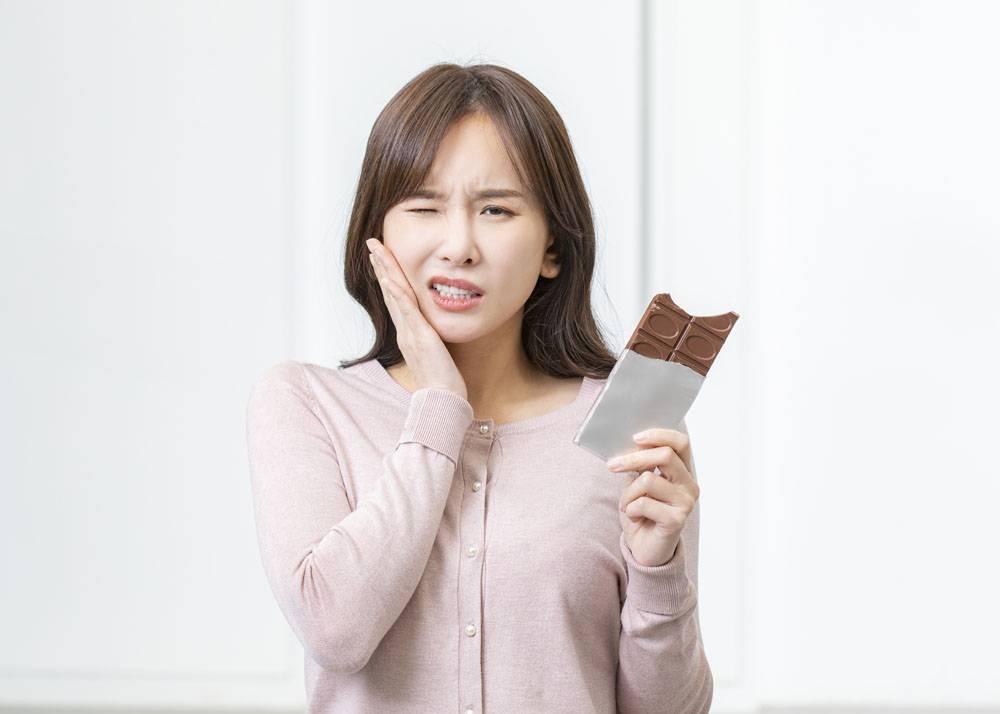 拿着巧克力板表示牙疼的女性