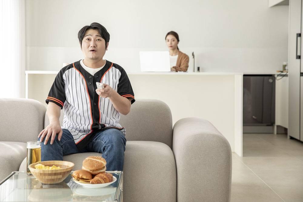 独自坐在沙发在家看电视棒球比赛的男子