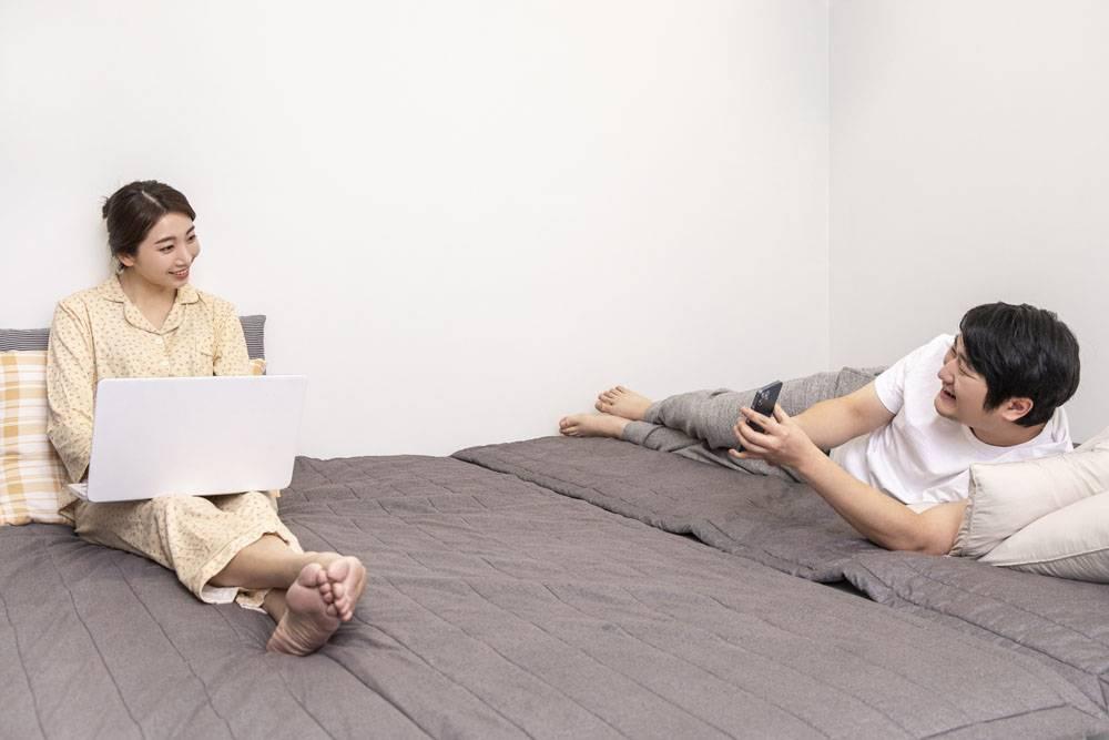躺在床上一个玩手机一个使用笔记本电脑的情侣