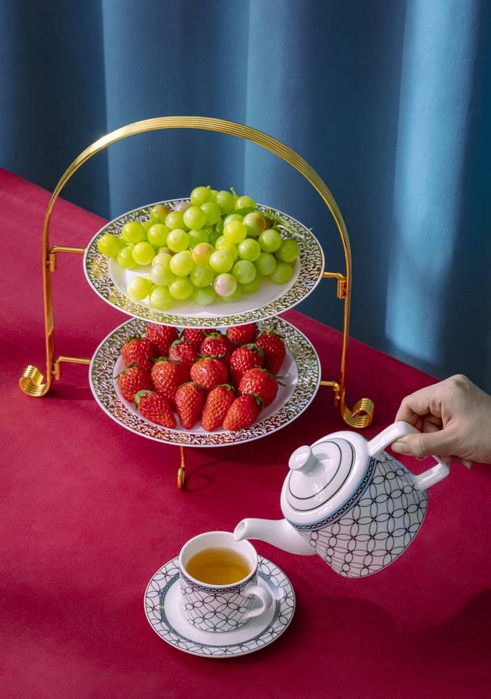 新鲜草莓葡萄与倒茶的茶杯茶壶