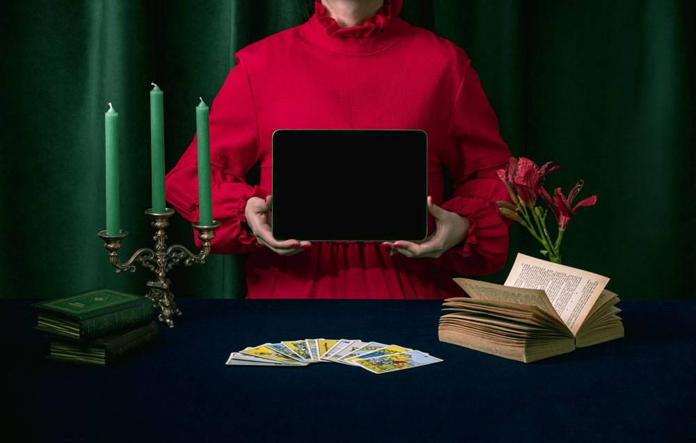 复古的书籍蜡烛票券与手持平板的女性