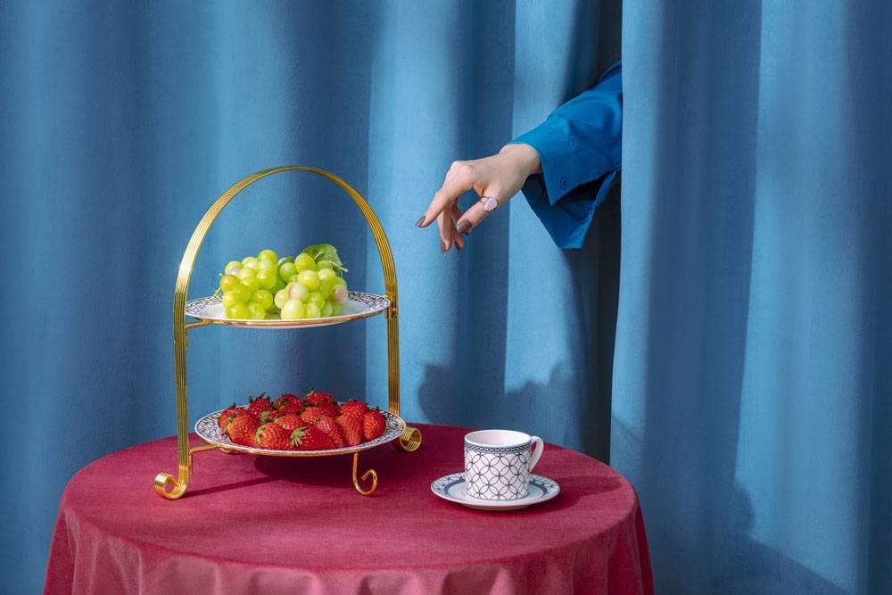 从窗帘伸手拿草莓和葡萄