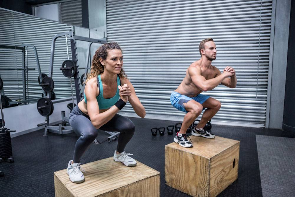 踩在木箱上半蹲的健身男女